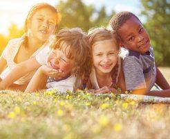 Multikulturelle Gruppe Kinder im Sommer liegt glücklich im Gras